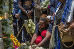 A Rwandan relative of a crash victim mourns at the scene where the Ethiopian Airlines Boeing 737 Max 8 crashed shortly after takeoff on Sunday killing all 157 on board, near Bishoftu, south-east of Addis Ababa, in Ethiopia Friday, March 15, 2019. Analysis of the flight recorders has begun in France, the airline said Friday, while in Ethiopia officials started taking DNA samples from victims' family members to assist in identifying remains. (AP Photo/Mulugeta Ayene)