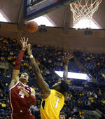Oklahoma center Jamuni McNeace (4) shoots while defended by West Virginia forward Derek Culver (1) during the first half of an NCAA college basketball game Saturday, Feb. 2, 2019, in Morgantown, W.Va. (AP Photo/Raymond Thompson)