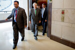 FILE - In this July 10, 2019, file photo, Senate Majority Leader Mitch McConnell of Ky., center, and Sen. Mike Rounds, R-S.D., right, arrive for a closed door meeting for Senators on election security on Capitol Hill in Washington.  While House Democrats are haggling over whether to consider impeachment of President Donald Trump, Senate Democrats are focusing on a different angle of former special counsel Robert Mueller's report _ securing future elections from foreign interference.(AP Photo/Andrew Harnik, File)