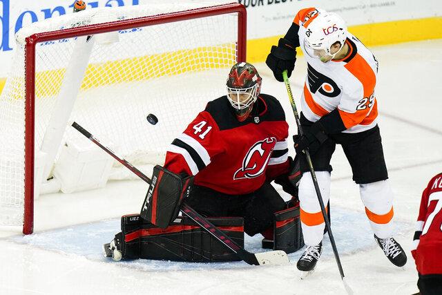 Philadelphia Flyers' James van Riemsdyk (25) scores a goal as New Jersey Devils goaltender Scott Wedgewood (41) defends during the second period of an NHL hockey game Tuesday, Jan. 26, 2021, in Newark, N.J. (AP Photo/Frank Franklin II)