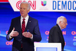 FILE - In this March 15, 2020, file photo Sen. Bernie Sanders, I-Vt., right, and former Vice President Joe Biden, left, return to the stage after a commercial break in a Democratic presidential primary debate at CNN Studios in Washington. White House contenders aren't typically bashful about asking for money. But as the coronavirus pandemic upends life, President Donald Trump and his likely Democratic rival, Biden, suddenly find themselves navigating perilous terrain. (AP Photo/Evan Vucci, File)