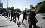 Riot police officers follow lawyers who try to walk to the parliament, in Ankara, Turkey, Friday, July 10, 2020. Turkey's Bar Associations continue to protest against the government's plans to amend laws regulating on lawyers and their associations. (AP Photo/Burhan Ozbilici)