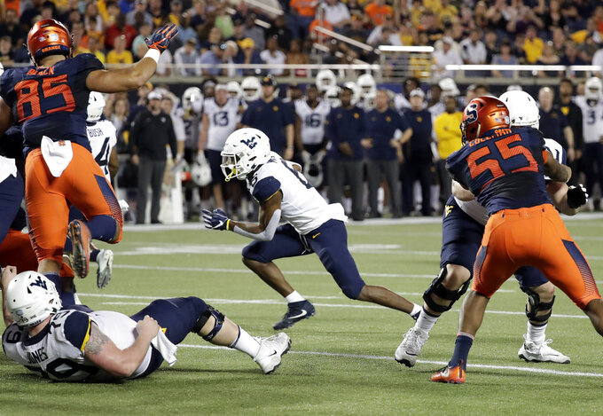 West Virginia running back Kennedy McKoy, center, slips past Syracuse defensive lineman Kendall Coleman (55) and defensive lineman Josh Black (85) for a 3-yard touchdown run during the first half of the Camping World Bowl NCAA college football game Friday, Dec. 28, 2018, in Orlando, Fla. (AP Photo/John Raoux)