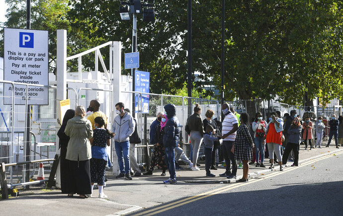 "People queue up outside a coronavirus testing centre offering walk-in appointments in north London, Friday Sept. 18, 2020. British Health Secretary Matt Hancock said Friday that the country has to ""come together"" over the coming weeks to get on top of the spike, that he noted is leading to a doubling in the number of people being hospitalized with the virus every seven to eight days. (Kirsty O'Connor/PA via AP)"