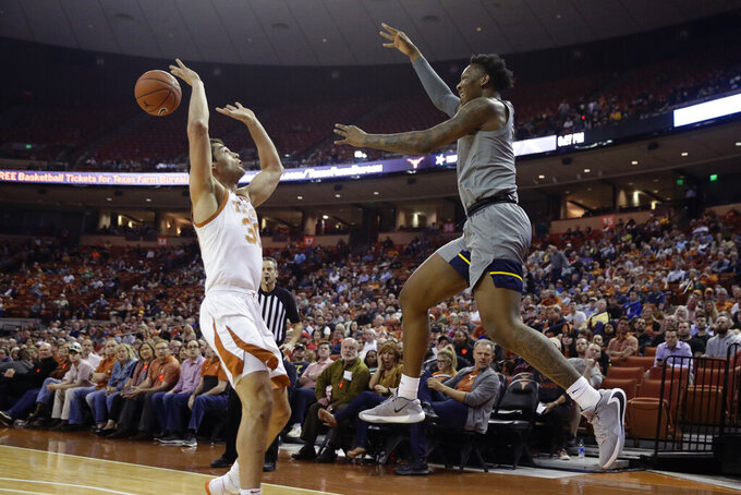 West Virginia forward Gabe Osabuohien, right, passes the ball over Texas guard Courtney Ramey (3) during the first half of an NCAA college basketball game, Monday, Feb. 24, 2020, in Austin, Texas. (AP Photo/Eric Gay)