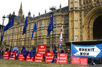 Pro Brexit placards and EU flags are pictured outside the Houses of Parliament, in London, Thursday, Sept. 5, 2019. Prime Minister Boris Johnson kept up his push Thursday for an early general election as a way to break Britain's Brexit impasse, as lawmakers moved to stop the U.K. leaving the European Union next month without a divorce deal. (AP Photo/Alberto Pezzali)