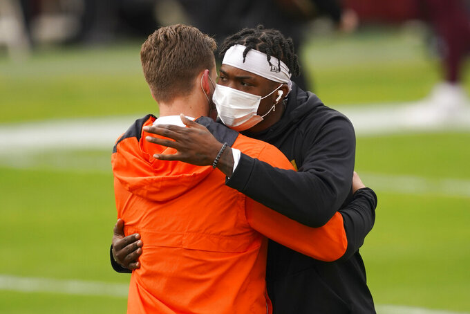 Cincinnati Bengals quarterback Joe Burrow, left, and Washington Football Team quarterback Dwayne Haskins, right, embrace on the field during pregame warm-ups before the start of an NFL football game Sunday, Nov. 22, 2020, in Landover, Md. (AP Photo/Andrew Harnik)