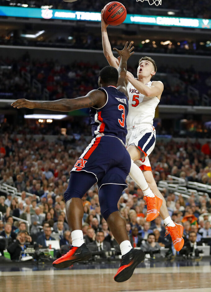 Virginia's Kyle Guy (5) takes a shot against Auburn's Danjel Purifoy (3) during the first half in the semifinals of the Final Four NCAA college basketball tournament, Saturday, April 6, 2019, in Minneapolis. (AP Photo/Jeff Roberson)