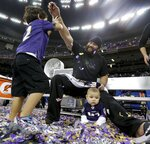 FILE - In this Feb. 3, 2013, file photo, Baltimore Ravens defensive end Haloti Ngata plays with two children after their 34-31 win against the San Francisco 49ers in the NFL Super Bowl XLVII football game, in New Orleans. Ngata came into the NFL with Baltimore and will leave as a member of the Ravens, the team that provided him with his best memories and a Super Bowl ring. (AP Photo/Patrick Semansky, File)