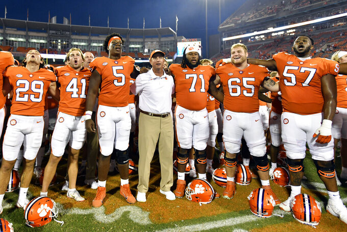 Clemson head coach Dabo Swinney, center, joins his team in singing the Clemson alma mater after an NCAA college football game against South Carolina State on Saturday, Sept. 11, 2021, in Clemson, S.C. (AP Photo/Edward M. Pio Roda)