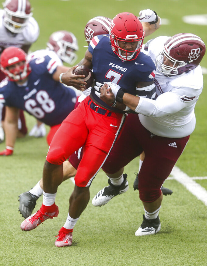 Liberty quarterback Malik Willis (7) carries the ball as he is tackled by Massachusetts linebacker Mike Ruane (33) and and defensive lineman Taishan Holmes (95) during the first half of a NCAA college football game on Friday, Nov. 27, 2020, at Williams Stadium in Lynchburg, Va. (AP Photo/Shaban Athuman)