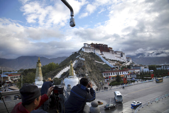 FILE - In this Sept. 19, 2015 file photo, tourists take photos of the Potala Palace beneath a security camera in Lhasa, capital of the Tibet Autonomous Region of China. A Tibetan man set himself on fire in a traditionally Tibetan area of China's Sichuan province and died in a protest Sunday, Nov. 4, 2018, a rights monitoring group reported. (AP Photo/Aritz Parra, File)