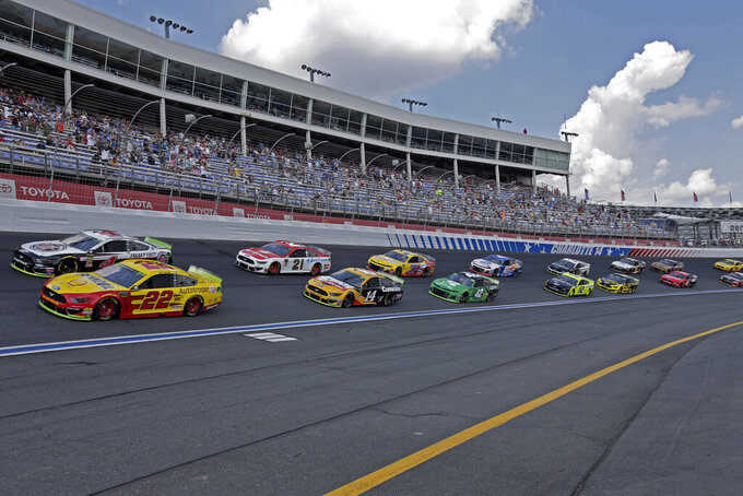 Cars drive through Turn 4 to start the NASCAR Cup Series auto race at Charlotte Motor Speedway in Concord, N.C., Sunday, Sept. 29, 2019. (AP Photo/Gerry Broome)