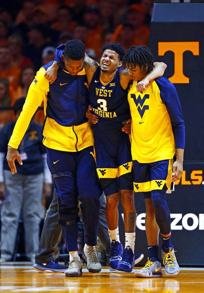 West Virginia guard James Bolden (3) is helped off the court after getting injured in the second half of an NCAA college basketball game against Tennessee, Saturday, Jan. 26, 2019, in Knoxville, Tenn. Tennessee won 83-66. (AP Photo/Wade Payne)