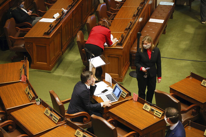 Minnesota House Speaker Melissa Hortman, standing, right, confers with Majority Leader Ryan Winkler, left, as the House met to take up several bills, including the insulin affordability bill, Tuesday, April 14, 2020 in St. Paul, Minn. (AP Photo/Jim Mone)