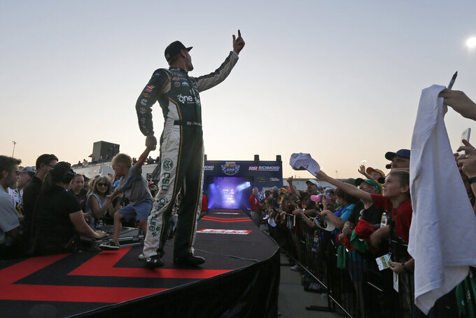Clint Bowyer (14) waves to the crowd as his son greets fans during driver introductions prior to the start of the NASCAR Monster Energy Cup series auto race at Richmond Raceway in Richmond, Va., Saturday, Sept. 21, 2019. (AP Photo/Steve Helber)