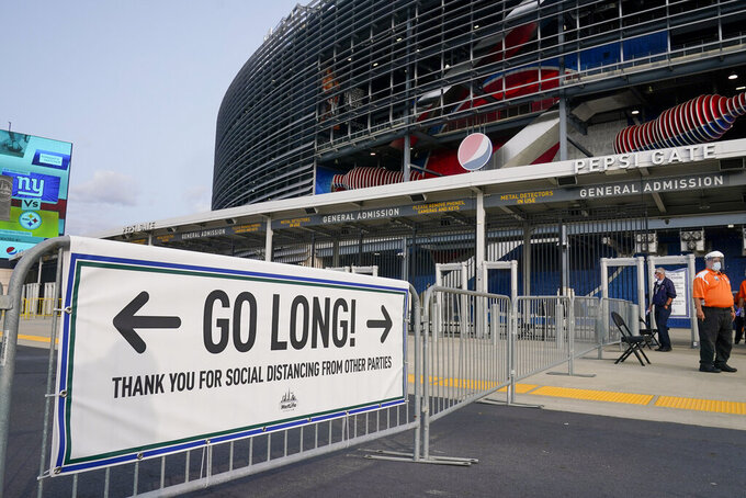 FILE  - In this Sept. 14, 2020, file photo, a sign reminding fans to maintain social distancing is shown outside Met Life Stadium before an NFL football game between the New York Giants and the Pittsburgh Steelers, in East Rutherford, N.J. A new set of rules are coming in just about every sport, almost all with enhanced health and safety in mind. If they work, games could get out of bubbles and return to arenas and stadiums with some fans in attendance sometime soon. Perhaps more importantly, they could also provide some common-sense solutions to virus issues in the real world. (AP Photo/Seth Wenig, FIle)