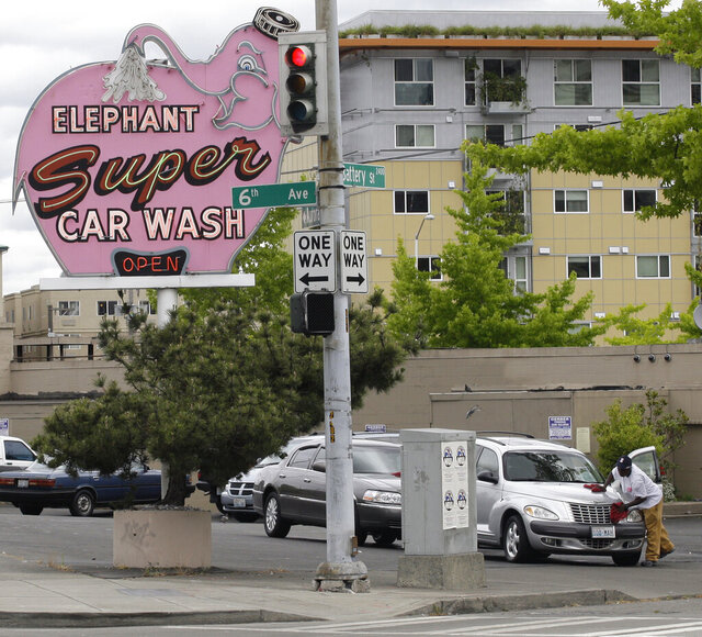 FILE - In this  July 8, 2009, file photo, a worker dries a car at Seattle's famous Elephant car wash, near the Space Needle in Seattle. Seattle's iconic pink elephant sign soon will have a new home. The Seattle Times reports the Elephant Car Wash on Battery Street near Denny Way will close permanently, the company announced in a news release Thursday, Oct. 8, 2020. (AP Photo/Ted S. Warren, File)
