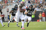 Tampa Bay Buccaneers running back Peyton Barber, center, runs for yardage past Jacksonville Jaguars free safety Jarrod Wilson (26) and defensive back Andrew Wingard (42) during the first half of an NFL football game, Sunday, Dec. 1, 2019, in Jacksonville, Fla. (AP Photo/Phelan M. Ebenhack)
