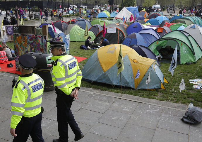 Police officers patrol past a village of tents during a climate protest at Marble Arch in London, Tuesday, April 16, 2019. The group Extinction Rebellion is calling for a week of civil disobedience against what it says is the failure to tackle the causes of climate change. (AP Photo/Kirsty Wigglesworth)