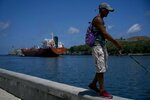 A fisherman walks on the Malecon seawall where an oil tanker can be see in the background in Havana, Cuba, Wednesday, April 17, 2019. Washington has sanctioned Venezuela's oil industry and shipping companies that move Venezuelan oil to Cuba. (AP Photo/Ramon Espinosa)