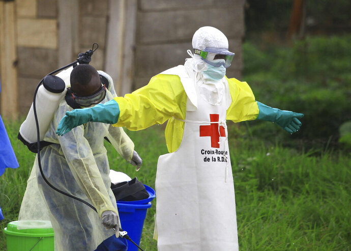 FILE - In this Sunday, Sept 9, 2018 file photo, a health worker sprays disinfectant on his colleague after working at an Ebola treatment center in Beni, eastern Congo.  Top Red Cross official Emanuele Capobianco said Friday April 12, 2019, that he's