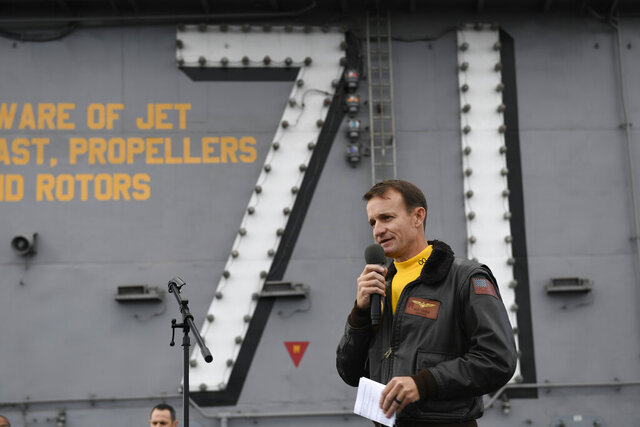 FILE - In this Nov. 15, 2019, file photo U.S. Navy Capt. Brett Crozier, then commanding officer of the aircraft carrier USS Theodore Roosevelt (CVN 71), addresses the crew during an all-hands call on the ship's flight deck while conducting routine operations in the Eastern Pacific Ocean. Crozier, the dismissed captain of the U.S. Navy aircraft carrier, knew he was jeopardizing his military career when he broke protocol and sent a now-famous email warning of possible sailor deaths due to a coronavirus breakout on board, but he did so in an urgent effort to help avoid a