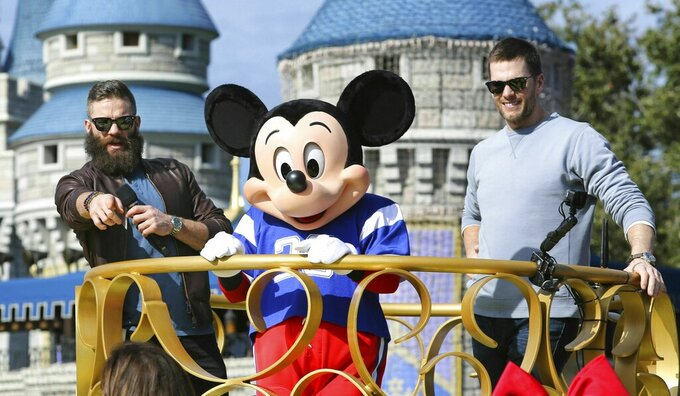 Super Bowl MVP Julian Edelman and Patriots quarterback Tom Brady (right) celebrate with Mickey Mouse in the Super Bowl victory parade in the Magic Kingdom, at Walt Disney World, in Lake Buena Vista, Fla., Monday, Feb. 4, 2019. (Joe Burbank/Orlando Sentinel via AP)