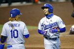 Los Angeles Dodgers' Mookie Betts, right, smiles as he celebrates his home run against the Arizona Diamondbacks with Dodgers' Justin Turner (10) during the fifth inning of a baseball game Sunday, Aug. 2, 2020, in Phoenix. (AP Photo/Ross D. Franklin)