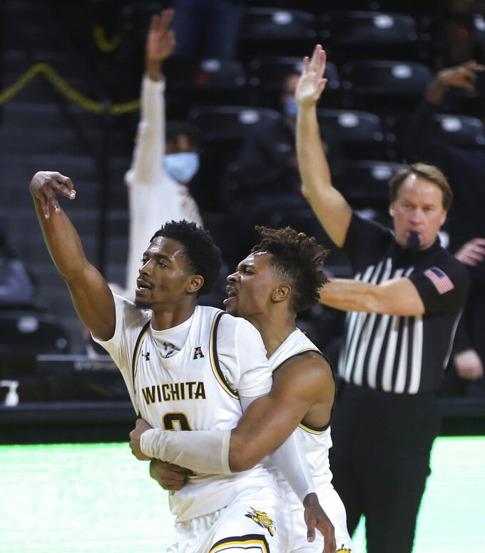 Wichita State's Alterique Gilbert, left, and Tyson Etienne celebrate after Gilbert hit a 3-pointer during the second half against Houston in an NCAA college basketball game Thursday, Feb. 18, 2021, in Wichita, Kan. (Travis Heying/The Wichita Eagle via AP)