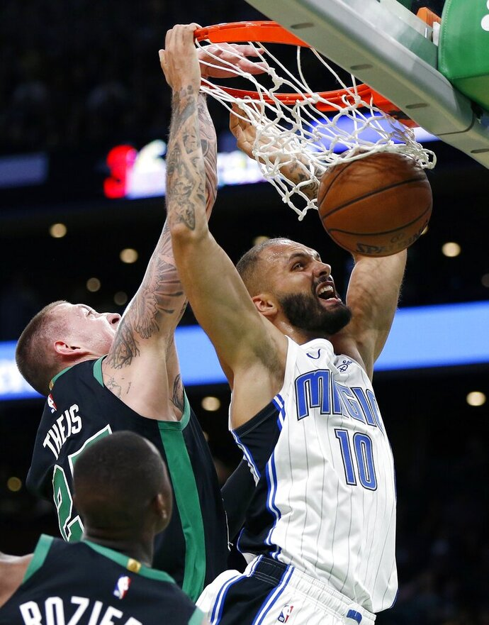 Orlando Magic's Evan Fournier (10) dunks against Boston Celtics' Daniel Theis (27) during the second half of an NBA basketball game in Boston, Sunday, April 7, 2019. (AP Photo/Michael Dwyer)