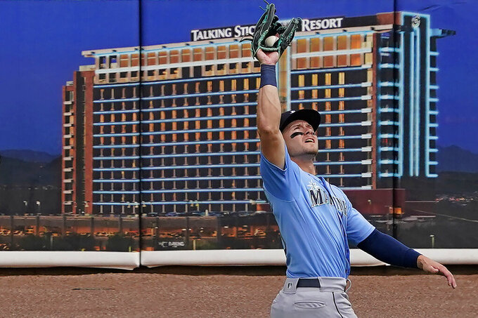 Seattle Mariners' Jarred Kelenic catches a fly-out hit by Oakland Athletics' Mark Canha during the first inning of a spring training baseball game, Thursday, March 25, 2021, in Mesa, Ariz. (AP Photo/Matt York)