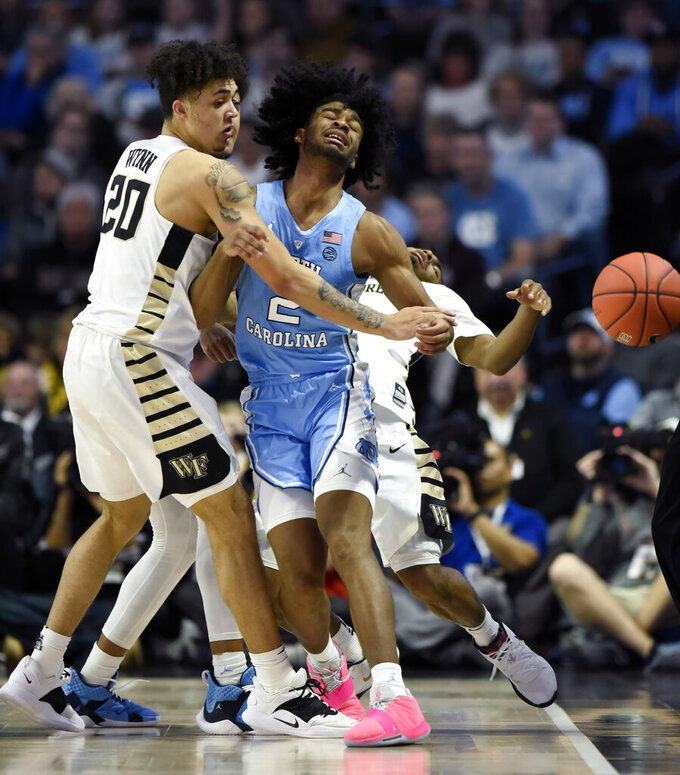 Wake Forest's Michael Wynn (20), Brandon Childress (0) and North Carolina's Coby White (2) collide as they all chase down a loose ball during the first half of an NCAA college basketball game in Winston-Salem, N.C.,  Saturday, Feb 16, 2019. (AP Photo/Woody Marshall)