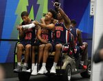 Auburn's Samir Doughty (10), Myles Parker (20) and Horace Spencer (0) get a ride after a practice session for the semifinals of the Final Four NCAA college basketball tournament, Thursday, April 4, 2019, in Minneapolis. (AP Photo/David J. Phillip)