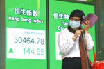 A woman wearing a face mask uses her mobile phone at a bank's electronic board showing the Hong Kong share index in Hong Kong, Tuesday, Feb. 23, 2021. Asian shares were mostly higher on Tuesday despite a sell-off in technology companies on Wall Street. (AP Photo/Kin Cheung)