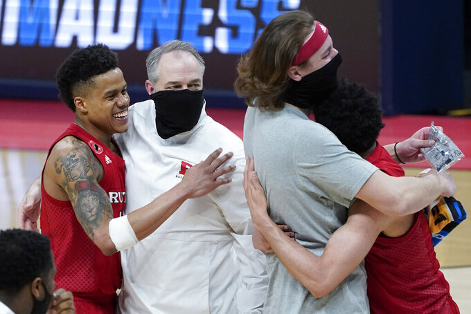 Rutgers guard Jacob Young, left, and head coach Steve Pikiell celebrate after beating Clemson 60-56 in a men's college basketball game in the first round of the NCAA tournament at Bankers Life Fieldhouse in Indianapolis, Friday, March 19, 2021. Rutgers won 60-56. (AP Photo/Paul Sancya)
