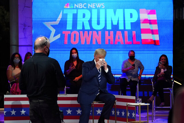 President Donald Trump wipes his face during a break in an NBC News Town Hall, at Perez Art Museum Miami, Thursday, Oct. 15, 2020, in Miami. (AP Photo/Evan Vucci)