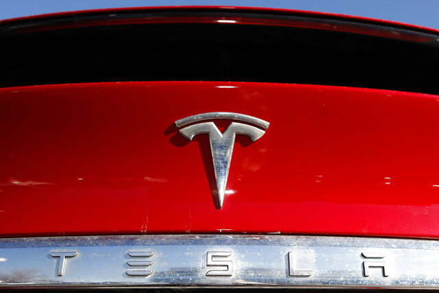 FILE - In this Feb. 2, 2020, file photo, the company logo appears on an unsold 2020 Model X at a Tesla dealership in Littleton, Colo.  The U.S. government's auto safety agency has rejected a request to investigate unintended acceleration in Tesla electric vehicles, saying the acceleration was caused by drivers pushing the wrong pedal.  (AP Photo/David Zalubowski, File)