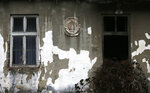 In this photo taken on Thursday, Jan. 23, 2020, an old Yugoslavian coat-of-arms is seen on an abandoned school building in the village of Blagojev Kamen, Serbia. Near-empty villages with abandoned, crumbling houses can be seen all over Serbia — a clear symptom of a shrinking population that is raising acute questions over the economic well-being of the country. The decline is happening so fast it's considered a national emergency and the United Nations has stepped in to help. (AP Photo/Darko Vojinovic)