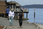 Gaye Scheel, left, and Kari Roberts wear masks as they walk, Tuesday, June 23, 2020, along Ruston Way in Tacoma, Wash. Gov. Jay Inslee announced that Washington state will require people to wear facial coverings in most indoor and outdoor public settings, under a statewide public health order in response to ongoing coronavirus-related health concerns. (AP Photo/Ted S. Warren)