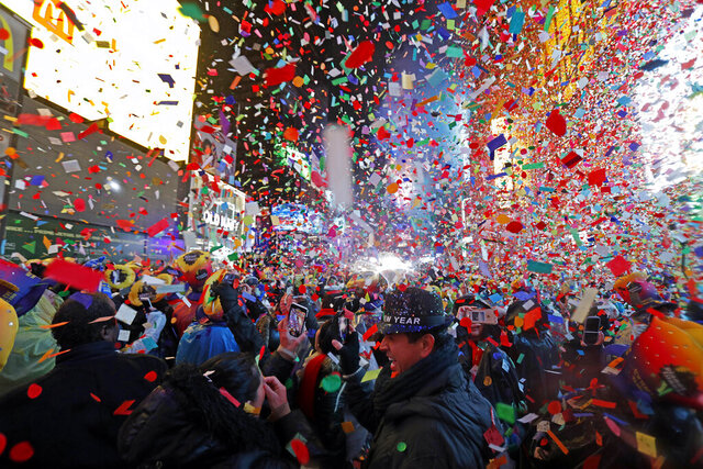 """FILE - In this Tuesday, Jan. 1, 2019, file photo, Joey Flores, of California, uses his cellphone as confetti falls during a New Year's celebration in New York's Times Square. New York City's counterterrorism czar expects Times Square to be """"the safest place on the planet Earth"""" on New Year's Eve. (AP Photo/Adam Hunger, File)"""