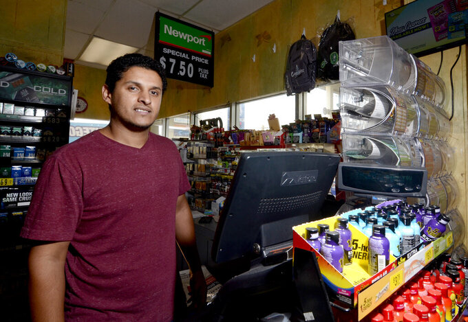 Store clerk Jacob Aziz, who sold an $80,000 winning lottery ticket, poses for a photo behind the register at the Express Way 2 at the corner of Delaware Avenue and Anna Drive in McComb, Miss., on Tuesday, Sept. 21, 2021. (Matt Williamson//The Enterprise-Journal via AP)