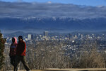 Hikers walk along a hiking path at the Kenneth Hahn Recreational area as heavy storm clouds and a dusting of snow are seen in the San Gabriel mountain range behind an area Los Angeles on Friday, Nov. 29, 2019.   Rain and snow showers are continuing in parts of the state Friday morning while skies are clearing elsewhere.(AP Photo/Richard Vogel)