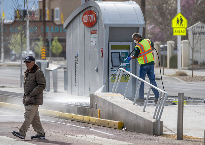 City crews clean a platform for the new ART bus system near Albuquerque, N.M.'s Old Town on Wednesday, March 18, 2020. Normally this area is booming with tourists because of spring break, but the recent coronavirus pandemic has forced visitors to stay away. (Roberto E. Rosales/The Albuquerque Journal via AP)