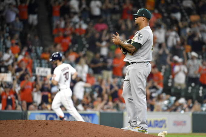 Oakland Athletics starting pitcher Frankie Montas, right, backs off the mound as Houston Astros' Kyle Tucker, back left, rounds the bases after hitting a solo run home run during the seventh inning of a baseball game, Saturday, April 10, 2021, in Houston. (AP Photo/Eric Christian Smith)