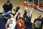 Texas guard Courtney Ramey (3) shoots past West Virginia guard Sean McNeil (22) during the first half of an NCAA college basketball game Saturday, Jan. 9, 2021, in Morgantown, W.Va. (AP Photo/Kathleen Batten)