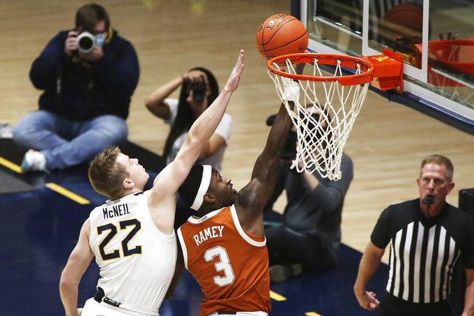 Texas guard Courtney Ramey (3) shoots past West Virginia guard Sean McNeil (22) during the first half of an NCAA college basketball game Saturday, Jan. 9, 2021, in Morgantown, W.Va. (AP Photo/Kathleen Batten)