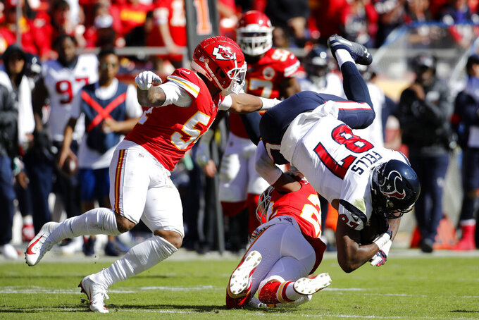 Houston Texans tight end Darren Fells (87) is upended by Kansas City Chiefs safety Juan Thornhill (22) and linebacker Damien Wilson (54) during the second half of an NFL football game in Kansas City, Mo., Sunday, Oct. 13, 2019. (AP Photo/Colin E. Braley)