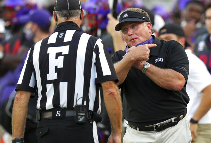 TCU head coach Gary Patterson, right, talks with an official during an NCAA college football game against Kansas State, Saturday, Oct. 10, 2020, in Fort Worth, Texas. (AP Photo/Richard W. Rodriguez)