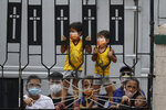 Young Catholic devotees wearing face masks to prevent the spread of the coronavirus stand try to get a glimpse of the the Black Nazarene at the Santa Cruz Church in Manila, Philippines a day before it's feast day on Friday Jan. 8, 2021. The annual Jan. 9 procession attended by tens of thousands of devotees has been cancelled amid the threat of the ongoing COVID-19 pandemic in one of Asia's biggest religious events. Several Black Nazarene replicas have been placed around churches as the government asks devotees to pray at their communities instead of going to downtown Quiapo where the original image stays. (AP Photo/Aaron Favila)